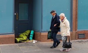 A man and woman walk past someone sleeping rough in a shop doorway in Glasgow.