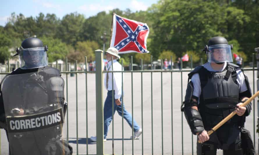 A man waves a Confederate flag in front of riot police.