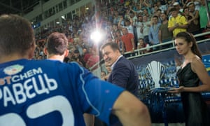 Mikheil Saakashvili presents the trophy and medals at the end of a cup final in Odessa