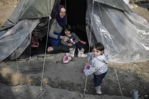 A Syrian woman sits in a tent with her children in the Vial refugee camp on the Greek island of Chios.