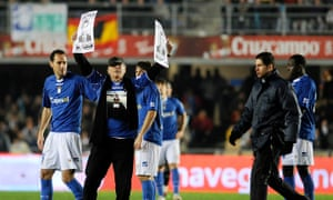 Francisco Holgado holds up pictures of his murdered son during a football match in Jerez in 2010.