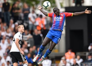 Fulham's German midfielder Andre Schurrle watches on as Crystal Palace's French midfielder Mamadou Sakho soars through the air at Craven Cottage.