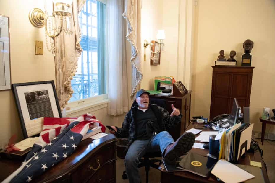 A supporter of Donald Trump sits inside the office of the speaker of the house, Nancy Pelosi.