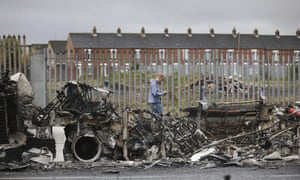 A man walks past a burnt out bus on the Shankill road in West Belfast, Northern Ireland.
