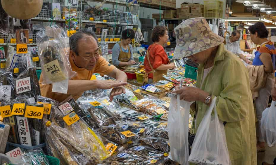 A woman does her shopping at a dried seafood market stall in Japan's Akita public market