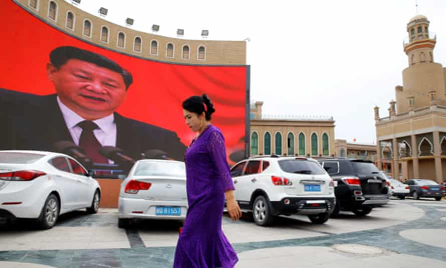 A Uyghur woman walks in front of a giant screen with a picture of Xi Jinping in Kashgar in Xinjiang, China.