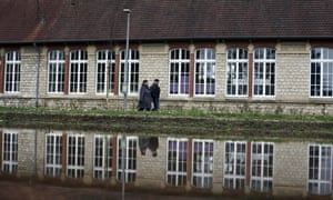 People walk past the Gerard de Nerval school, which has been closed since 2 March, in Crepy en Valois, northern France