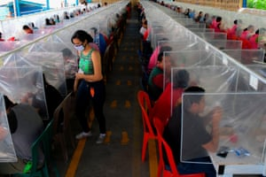 Workers at the factory have lunch separated by plastic panels as a preventive measure against the spread of Covid-19.