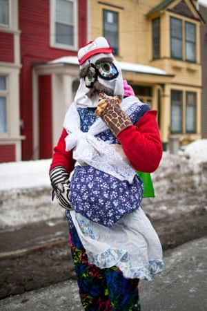 Pavement-side shot of a mummering, St John's, Newfoundland. This mummerer is looking to the camera, on a cold winter's day, but is masked and wearing an assortment of strange and colourful clothing. Although the tradition is now associated with fun and tomfoolery, this hasn't always been the case. Mummers often carried large sticks or other weapons, and between the 1830s and 1860s there were a number of reports of violence.
