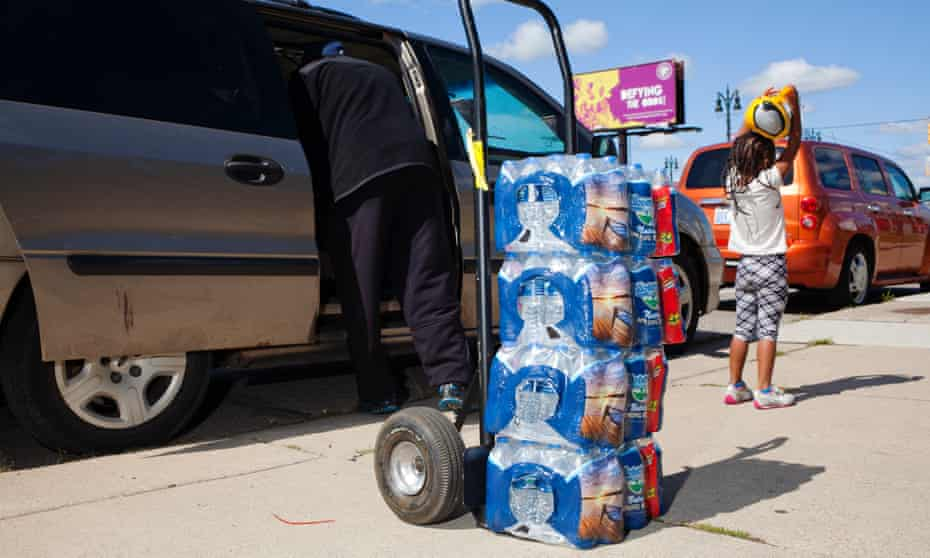 A volunteer loads bottles of water into the car of a family whose water has been shut-off.