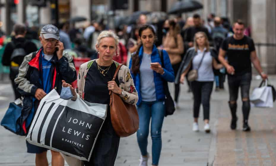 Shoppers walking along Oxford Street carrying their purchases