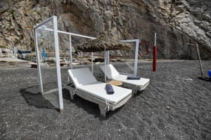 Plexiglass panels protect an umbrella and sunbeds on a beach in Santorini, Greece