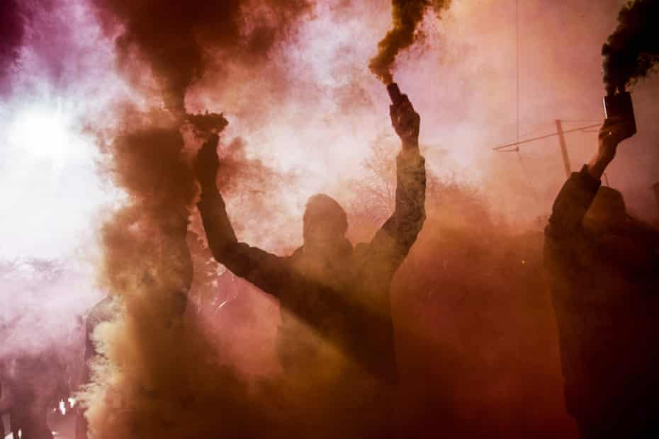 Demonstrators hold up flares during a gilets jaunes (yellow vest) protest in Paris against Emmanuel Macron's government.