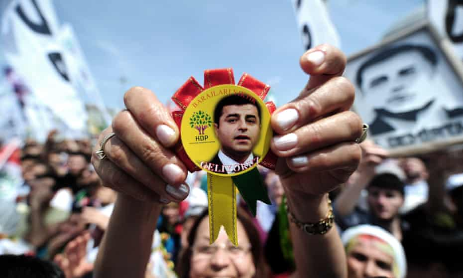 A woman shows a badge bearing the face of Selahattin Demirtaş, leader of the Peoples' Democratic party, during an election rally in May. The party went on to win 80 seats in parliament.