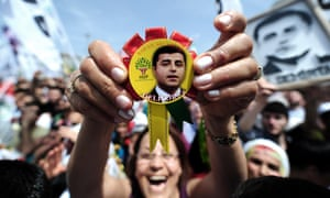 A woman shows a badge of pro-Kurdish Peoples' Democratic Party (HDP) Selahattin Demirtas in the district of Bağcılar in Istanbul on May 24, 2015 during an election rally.