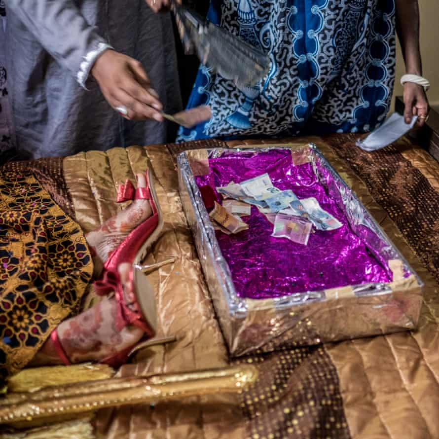 Wedding guests leave money in a box at the foot of the bride's bed on the morning of her marriage