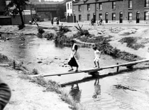 A woman and a girl crossing the river on a temporary bridge , Mill Road , Lewisham , London 1938