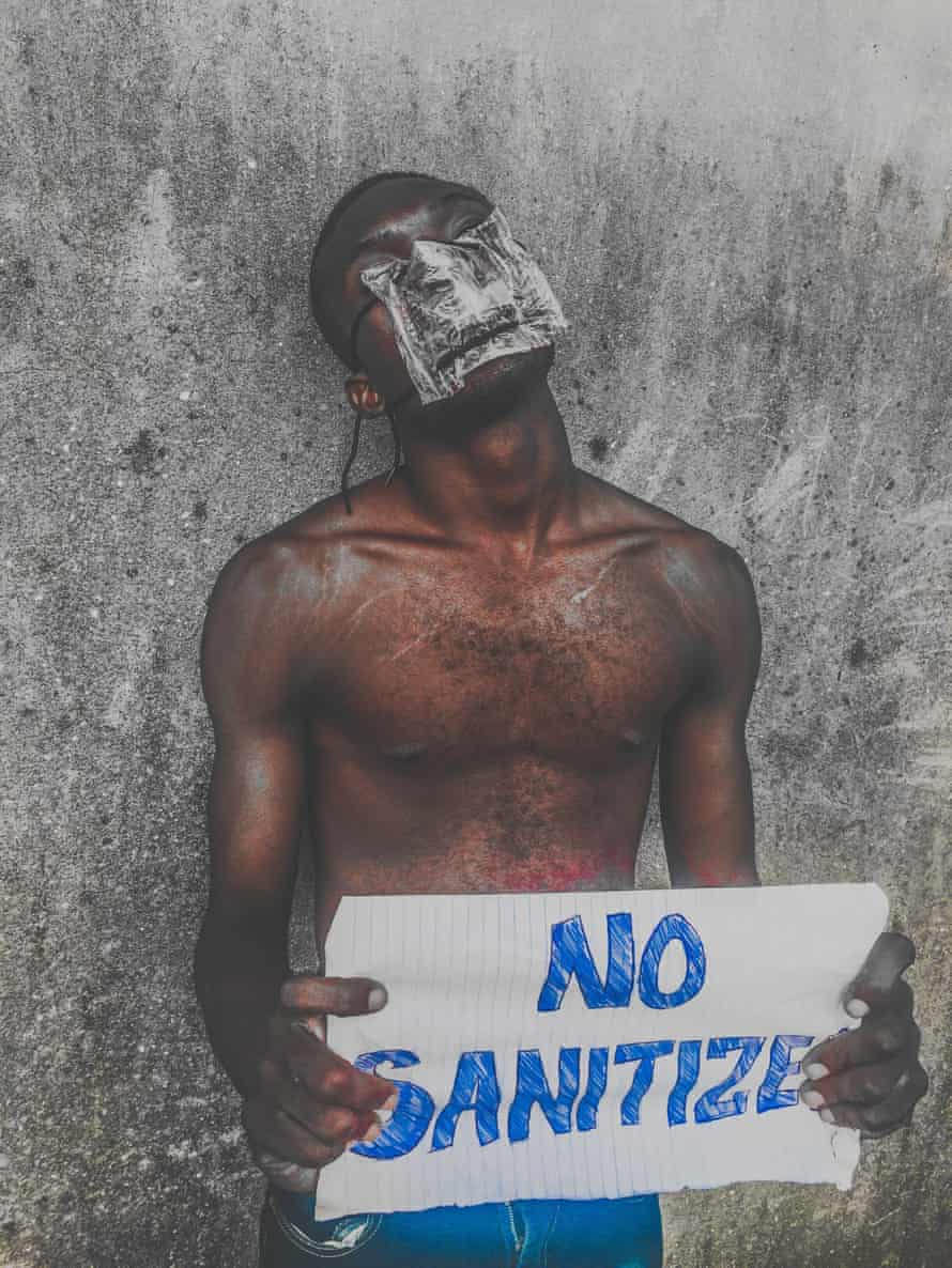 Wearing a mask made from plastic water sachets, a boy holds a sign in Orile.