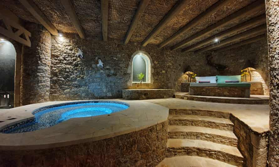 A pool inside a dark, stone building with steps and loungers