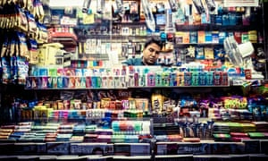 A man works at a small street shop in New York City.