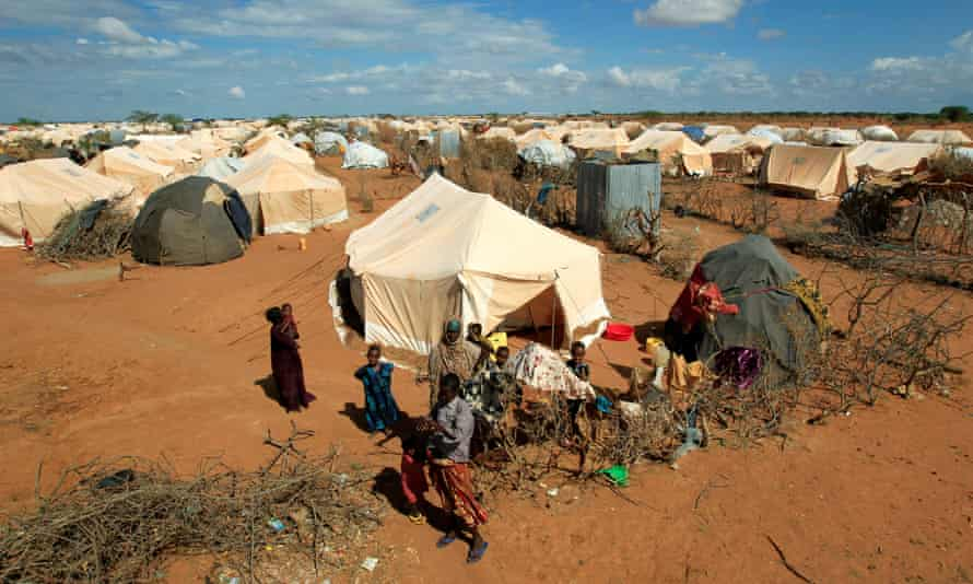 Refugees stand outside a tent at the Dadaab refugee camp