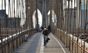 People ride bicycles on a nearly empty Brooklyn Bridge.