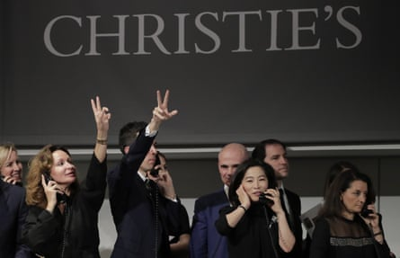 Bidding representatives motion for a bid on Armand Seguin's Les delices de la vie during an auction from the collection of Peggy and David Rockefeller in New York, 8 May 2018.