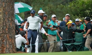 Tiger Woods hops through the crowd after the collision with a security guard during his second round at the Masters.