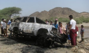 People gather at the site of a drone strike on the road between Yafe and Radfan districts of the southern Yemeni province of Lahj August 11, 2013.