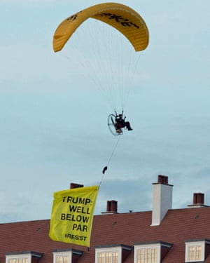 A Greenpeace protester paraglides over Donald Trump's resort in Turnberry.