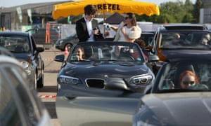 """Visitors in cars drink champagne as they attend a drive-in live broadcast of the Berlin state opera performing Giacomo Puccini's """"La fanciulla del West."""""""