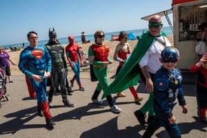 A group dressed as superheroes walk down a promenade in Bognor Regis.
