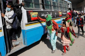 A migrant worker holds her daughter's hand as she tries to board a bus, 29 March