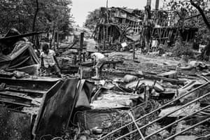 Children sift through the wreckage of homes destroyed during rioting
