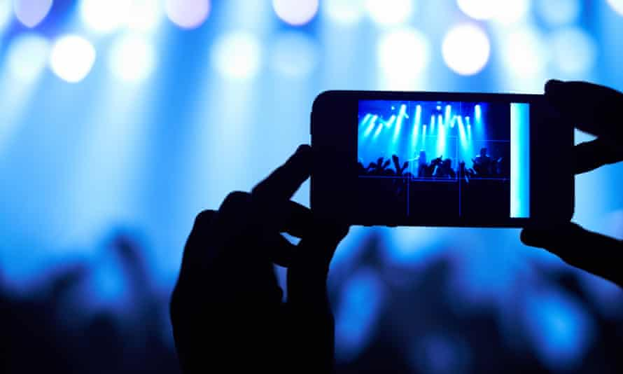 Cropped shot of a person filming their favorite band with a camera phone.