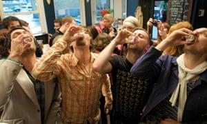 Young men doing shots in a pub