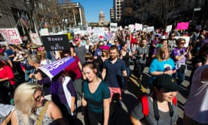 Protesters march down Congress Street in Austin as they take part in the Austin Women's March.