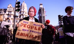 A girl wearing a paper mask of the Queen joins the climate protest in Parliament Square, London