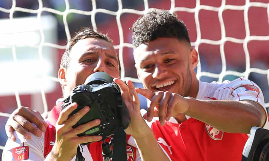 Alex Oxlade-Chamberlain, right, borrows a photographer's camera for a selfie with team-mate Santi Cazorla after winning the Community Shield.