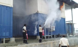 Immigration officers and police try to extinguish a blaze at Manus Island refugee accommodation after a man set himself on fire inside