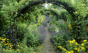 Pergola s and a variety of plants surround a pathway as it leads through the Walled Garden at Wallington