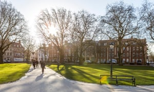 Queen Square, Bristol. A handful of people walk through a green space in the centre of the square as early morning sunlight breaks through bare trees.