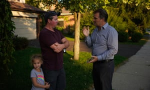 Green party candidate Steve Dyck, right, chats with a voter as he canvasses a neighbourhood in Guelph ahead of Canada's federal election on 21 October.