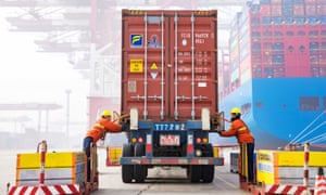 Workers prepare a container at the port in Qingdao, China