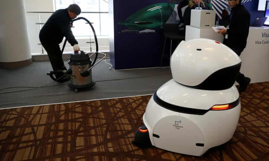 A robot carpet cleaner passes a worker using a traditional vacuum cleaner in the main press centre.