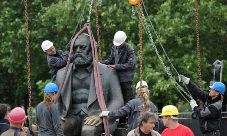 Workers lift a statue of Marx  off its base in Berlin   allow for work on a new underground line.
