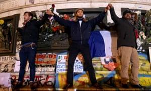 Three men are seen singing the French national anthem on the Place de la République monument.