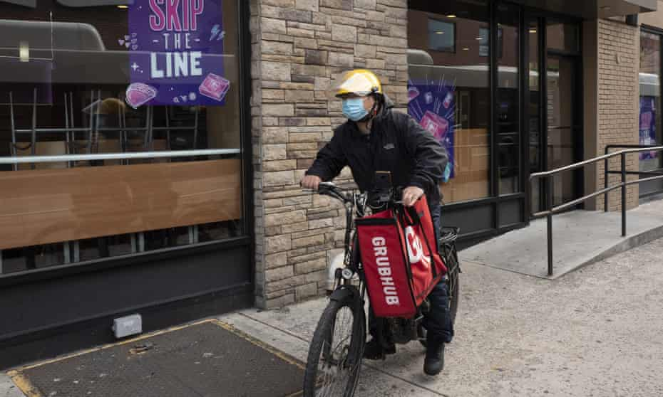A Grubhub food delivery worker bikes through New York City.