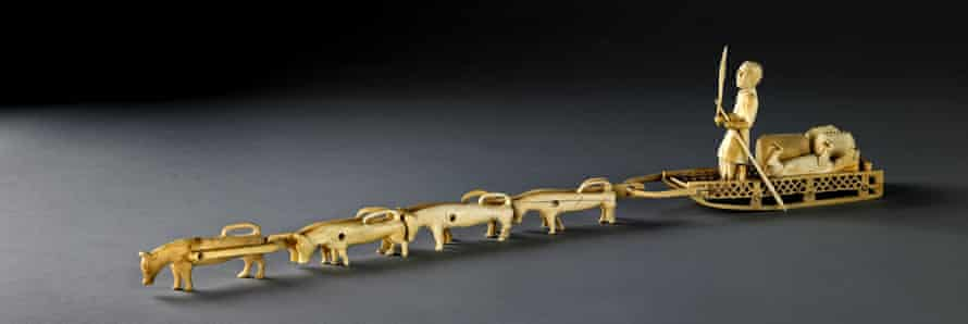 A carved ivory model of a dog sled.