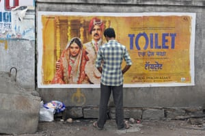 In Hyderabad, an Indian man urinates on a roadside wall in front of a poster for the Hindi film Toilet.